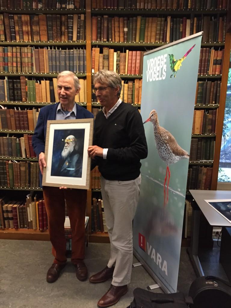 Links Louis Schoonhoven (hoofdauteur) en rechts Rolf Roos (boekbezorger) uitreiking Jan Wolkersprijs 18 oktober 2015 in de Artis Bibliotheek; beeld Darwin met bloemen- en beestenkrans van de hand van Siegfrid Woldhek